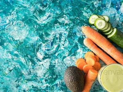 Top view of detox juice next to carrots, cucumber and avocado