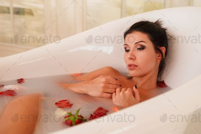 Young attractive woman relaxing in bath with foam and petals.