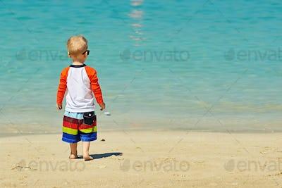 Two year old toddler boy walking on beach