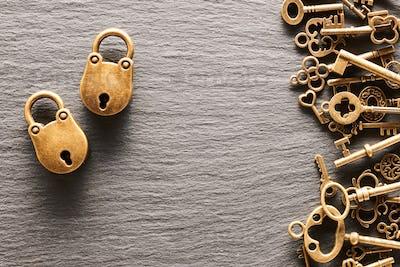 Various metal keys and locks on slate background