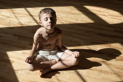 Charming little boy is while doing yoga at home