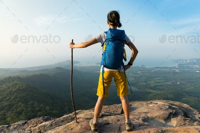 Successful hiker stand on mountain top cliff edge