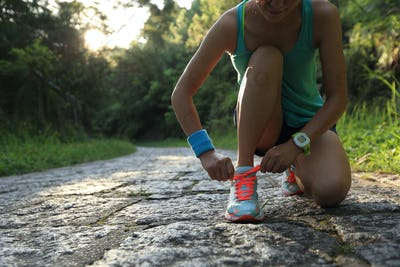 Trail runner tying shoelace on forest trail