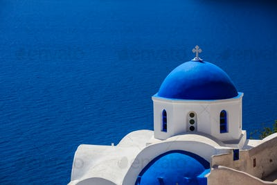 White church with blue dome in Santorini, Greece