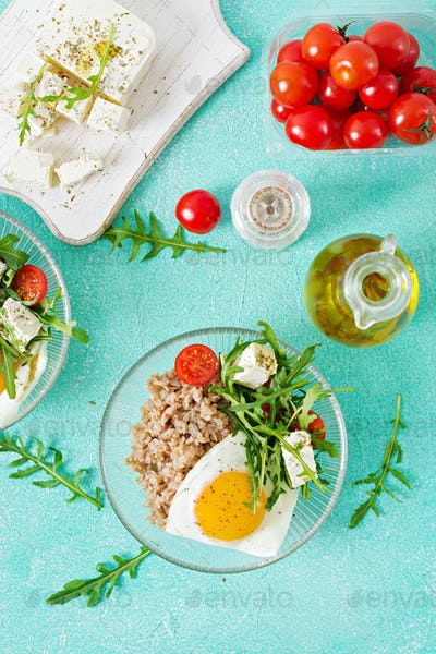 Healthy breakfast with egg, feta cheese, arugula, tomatoes  and buckwheat porridge