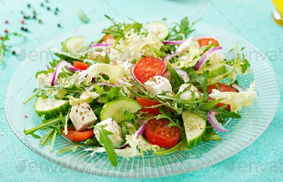 Salad of fresh vegetables - tomato, cucumber and feta cheese in Greek style