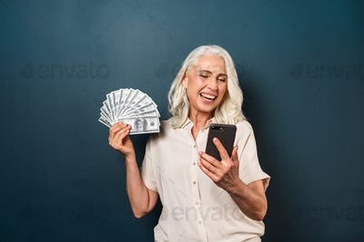 Mature happy old woman holding money using mobile phone.