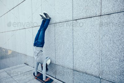 Hipster handstand on skateboarder