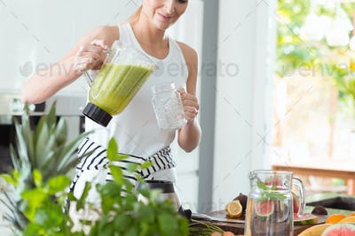 Happy woman pouring green cocktail