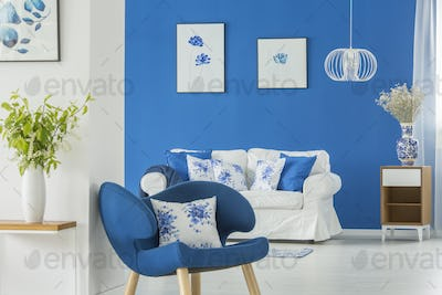 Blue armchair by white wall