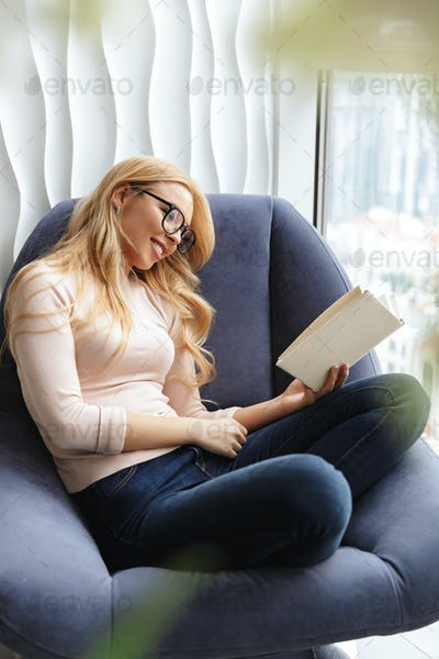 Beautiful young woman indoors at home reading book