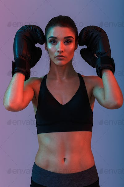 Photo of sexual slim woman 20s in sportswear and black boxing gl