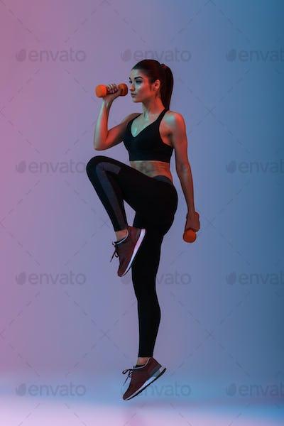Full length portrait of sportswoman in tracksuit doing exercises