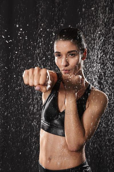 Сaucasian athletic woman wearing black sportive bra punchning w