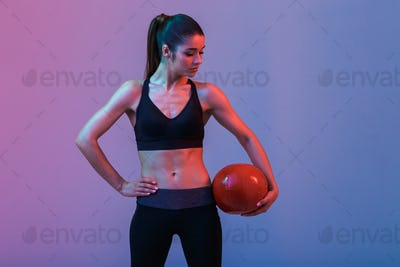 Strong young sports woman standing with ball