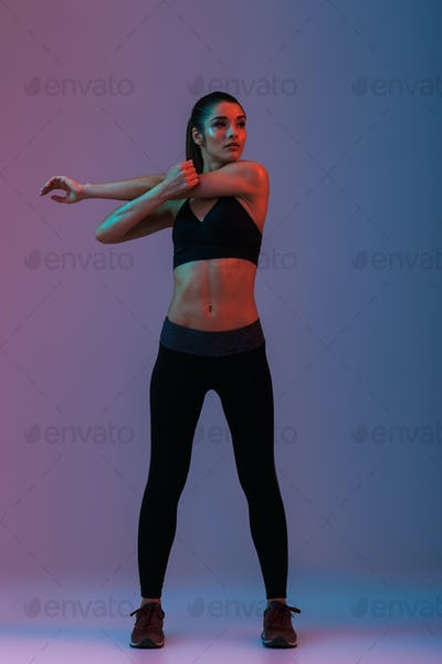 Full length portrait of sportswoman in fitness clothing looking