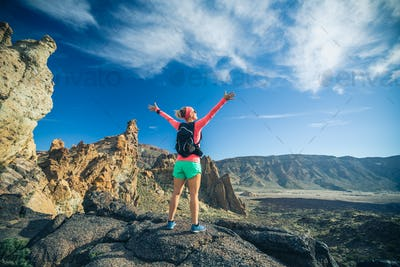 Woman hiker with arms outstretched enjoy mountains