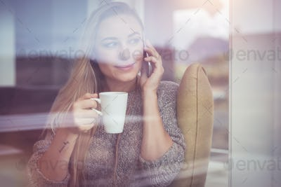 On the phone with cup of tea
