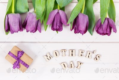 Bouquet of purple tulips and gift for mother's day on white boards