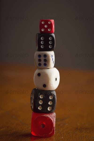 different size and color rolling dices on wooden background