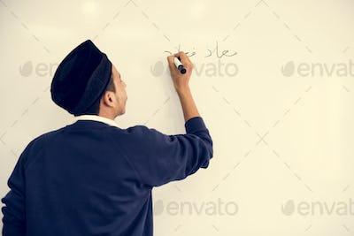 Young muslim man is writing a white board