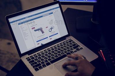 Closeup of hand ordering gun online