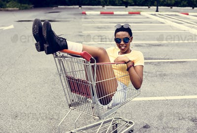 An African Descent woman sitting in a shopping trolley