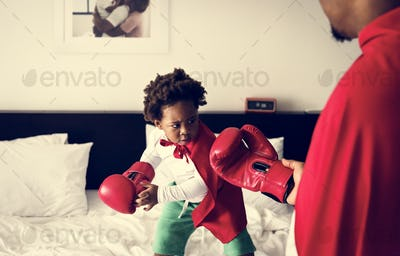 African descent kid wearing robe doing boxing with dad on the bed