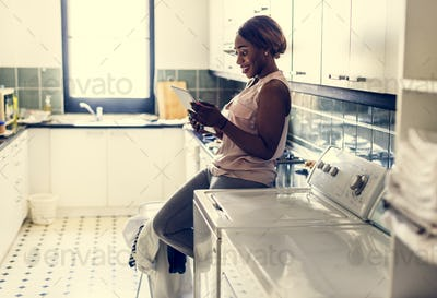 Black woman using digital tablet near the washing machine