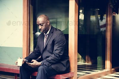 Businessman sitting alone working on phone