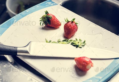Closeup of fresh strawberries on cutting board with knife at sink