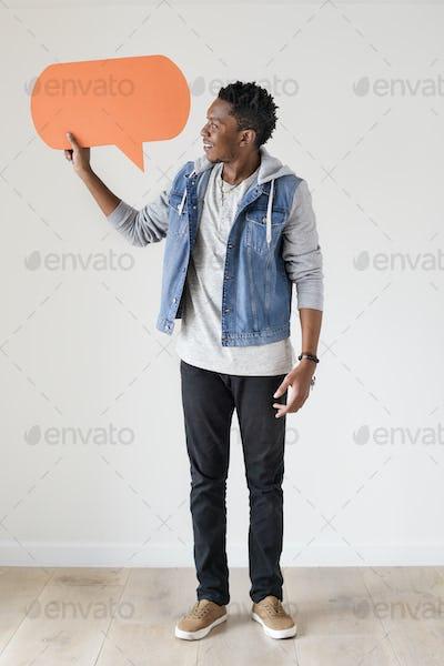 Happy African American man holding copyspace speech bubble