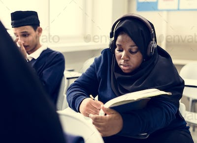 diverse muslim children studying in classroom