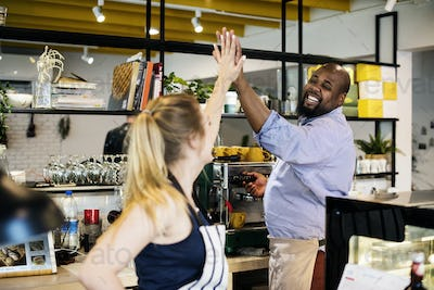 Colleagues give a high five to each other
