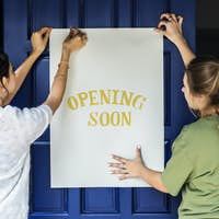 Women putting on store opening soon sign