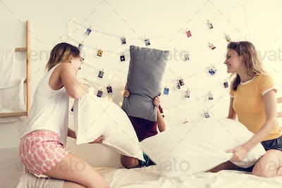 A diverse group of women playing pillow fight on bed together