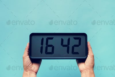 Hands holding digital clock isolated on background