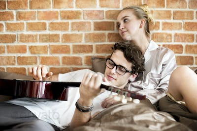 Caucasian couple on the bed, man playing a guitar