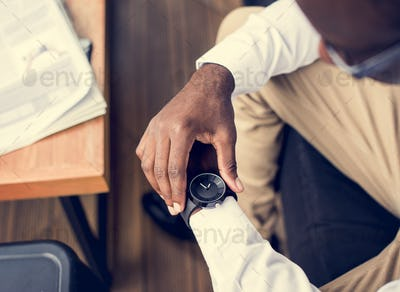 African ethnicity man sitting watching a watch