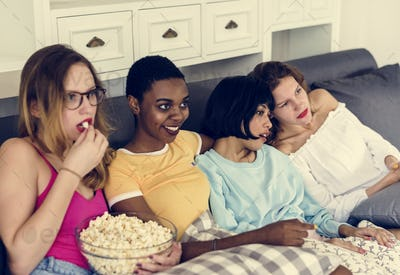 Diverse women eating popcorn together