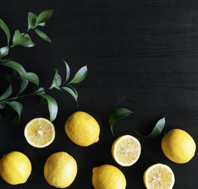 Fresh yellow lemons on black background