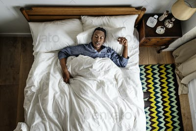 Black man sleeping on bed