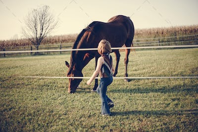 Little girl playing with a horse