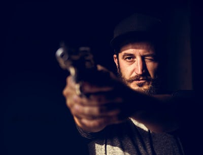 Man holding a gun wth black background