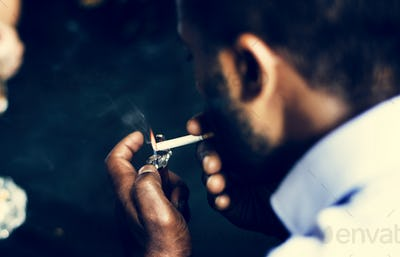 Rear view of man lighting up the cigarette in his mouth