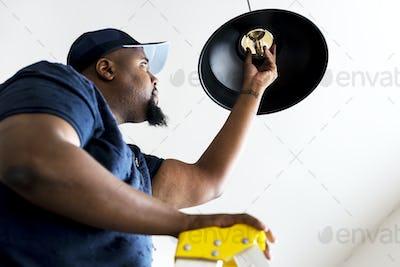 Man changing light bulb lamp