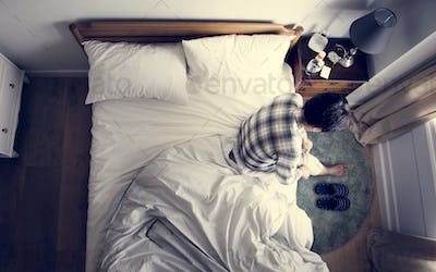 Injured Asian man sitting on the bed