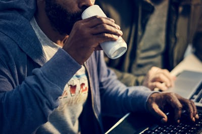 Hacker drinking a can beverage while working