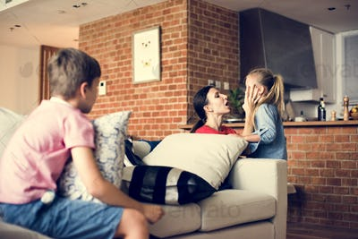 Mother consoling daughter and son sitting on the couch