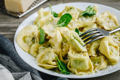 Italian ravioli pasta with spinach and ricotta on wooden background